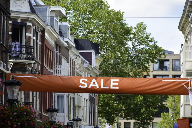 Big red sale label banner. Discount sign with white text above shopping centre district. Utrecht, The Netherlands - AUGUST 7 2019: Big red sale label banner royalty free stock photography