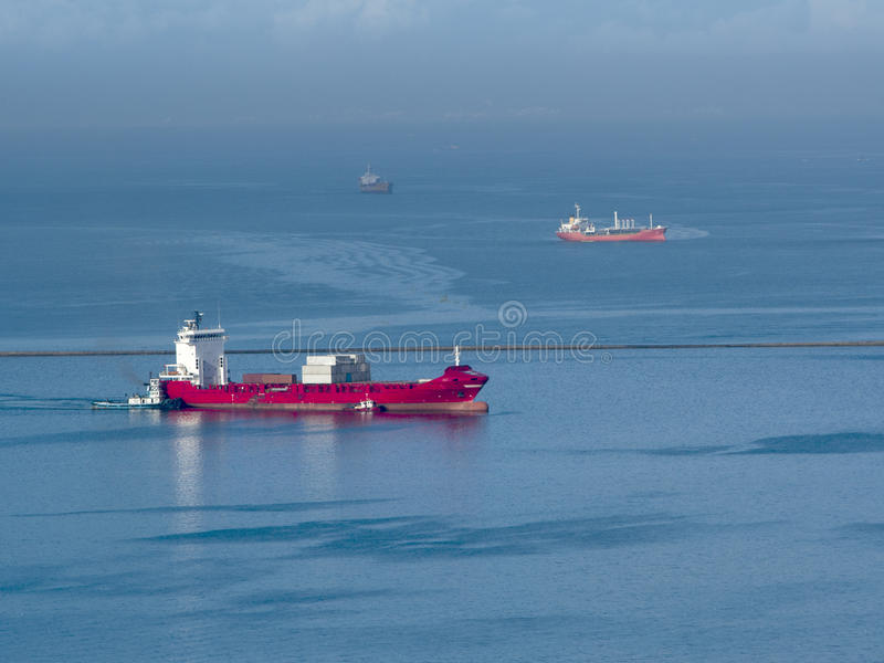 Big red ship in the sea. Big red container ship transporting cargo and being escorted by a tugboat in the ocean royalty free stock photography