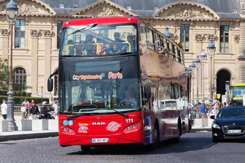 PARIS, FRANCE - JUNE 23, 2017: Big red tourist bus with the passengers on the road near the famous Louvre Palace in summer day royalty free stock image