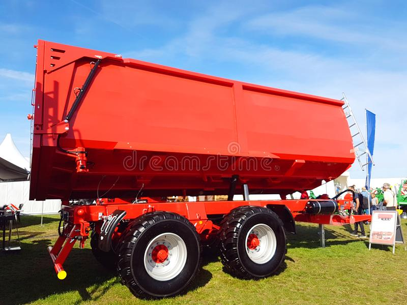 Big red trailer for loading with wheat. For transport during harvest season royalty free stock photo