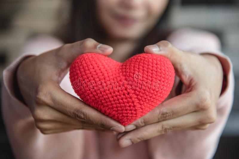 Big red yarn heart holding and giving to front by woman hand. Love and affection in Valentines day concept. Romantic object and stock image