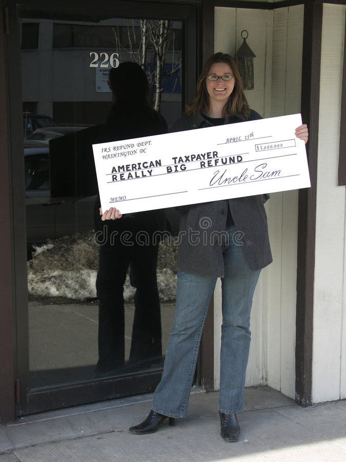Big Refund. Smiling woman holding an oversize tax refund check. Focus on the check stock photo