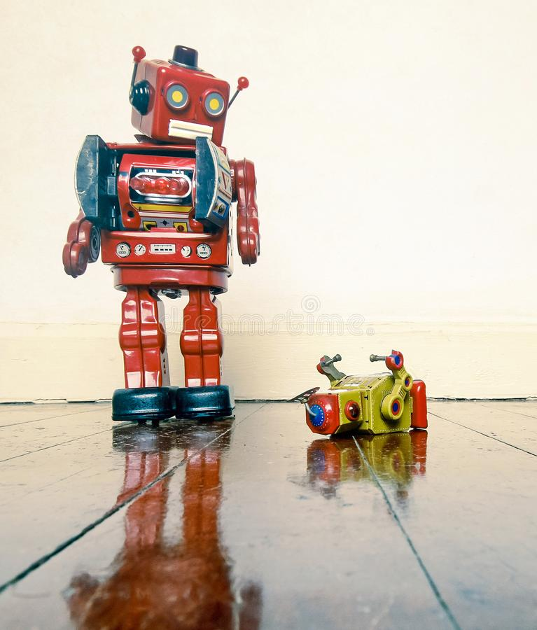 Big robot humiliates liitle one. Big retro robot toy humiliates little robot on a wooden floor with reflection royalty free stock photography