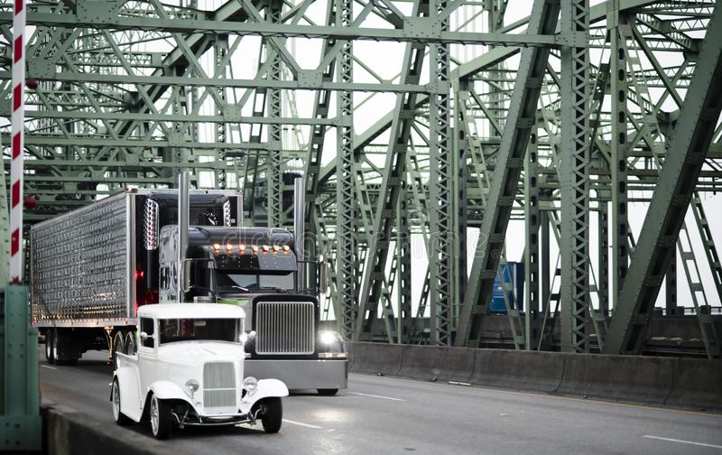 Big rig black classic semi truck with refrigerator semi trailer royalty free stock photos