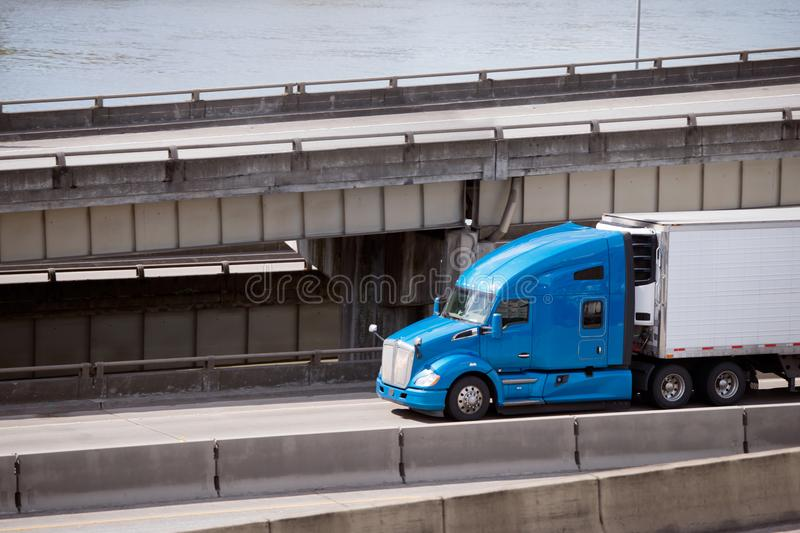 Big rig blue pro semi truck transporting reefer semi trailer on. Big rig blue American pro semi truck transports reefer semi trailer with refrigerated perishable royalty free stock photos