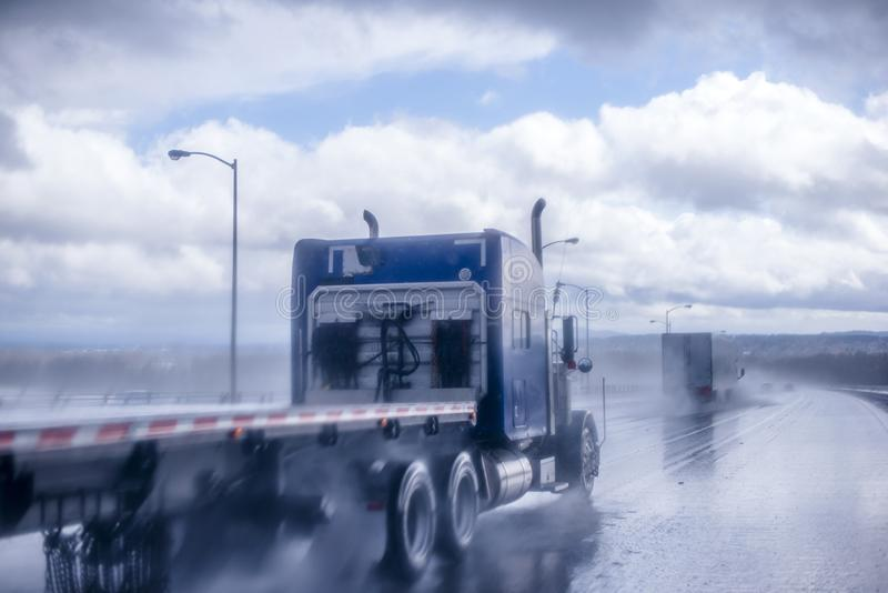 Big rig blue classic semi truck with flat bed semi trailer moving on the wet raining road behind another semi truck with rain dust. Big rig blue American classic stock photography