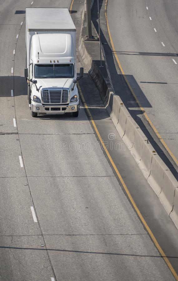 Big rig bonnet semi truck transporting cargo in dry van semi trailer driving on the left line on wide highway in sunny day. Big rig white long haul bonnet royalty free stock photography