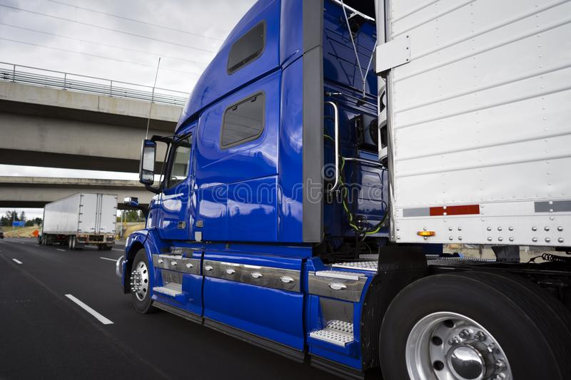 Big rig bright blue long haul semi truck transporting goods in r. Big rig modern bright blue long haul semi truck with refrigerator semi trailer transporting royalty free stock photography