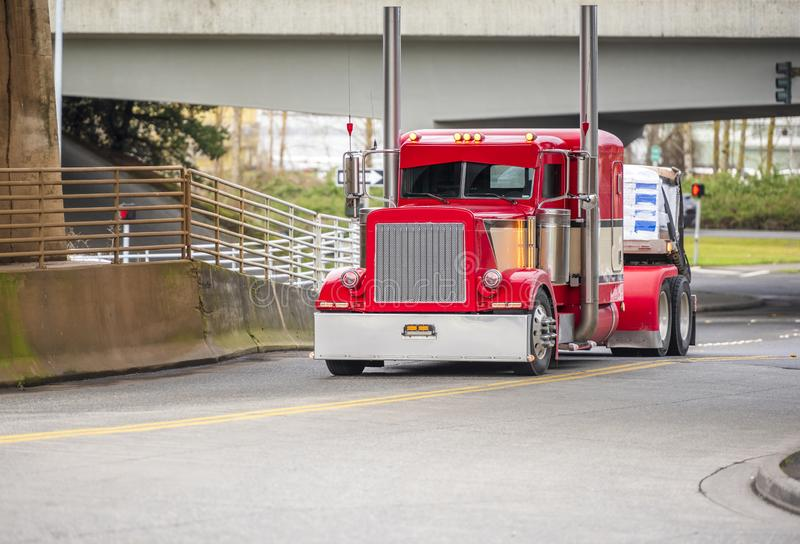 Big rig bright red classic American idol semi truck for long haul routs with high chrome exhaust pipes transporting semi trailer. Driving on the city street royalty free stock photography