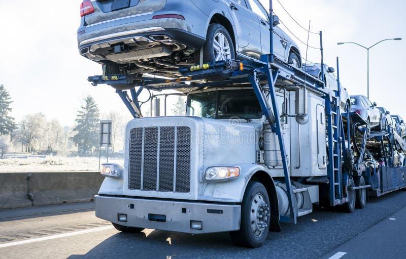 Big rig car hauler semi truck transporting cars on two levels semi trailer driving on winter frosty road. Big rig car hauler professional bonnet powerful semi stock images