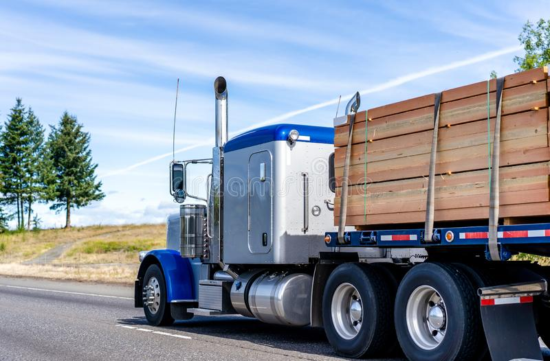 Big rig classic blue bonnet semi truck tractor transporting lumber wood on flat bed semi trailer on the road with hill on the side. Big rig classic American blue stock photography