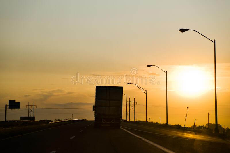 Big Rig Drives toward Sun. A Big Rig Drives toward Sunrise/Sunset on US Interstate Highway stock images