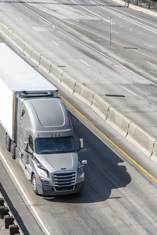 Big rig gray bonnet semi truck transporting cargo in refrigerator semi truck driving on the divided wide highway. Big rig gray long haul bonnet professional royalty free stock image