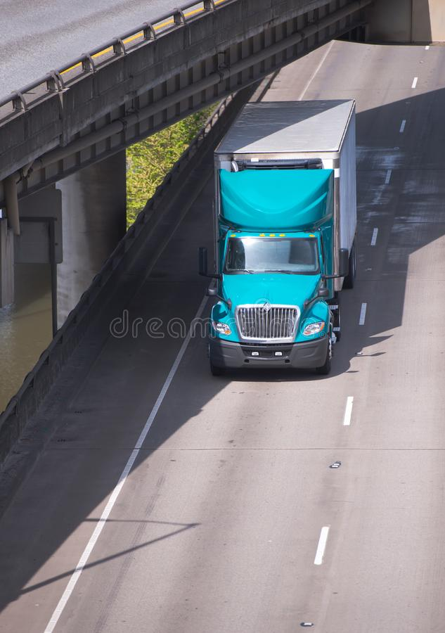 Big rig semi truck with reefer unit on semi trailer driving on e. Big rig green long haul semi truck with reefer unit on refrigerated semi trailer driving on stock photos