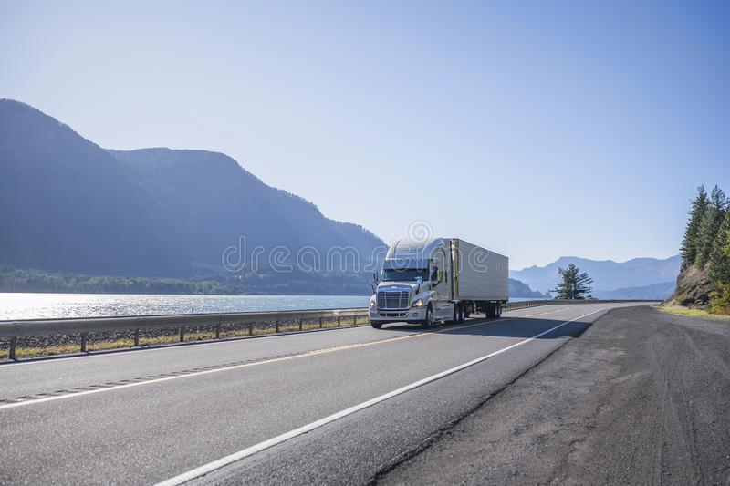 Big rig professional popular semi truck tor long haul freight transporting cargo in refrigerator semi trailer running on the road. Big rig white professional stock photos