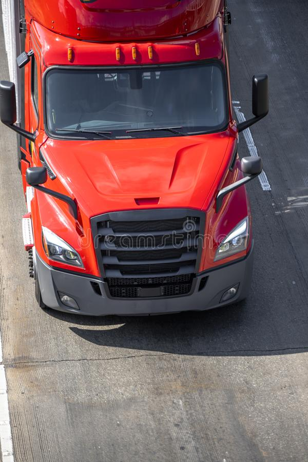 Big rig red semi truck tractor with semi trailer driving on the wide road. Big rig red long haul bonnet professional heavy-duty semi truck transporting stock photos