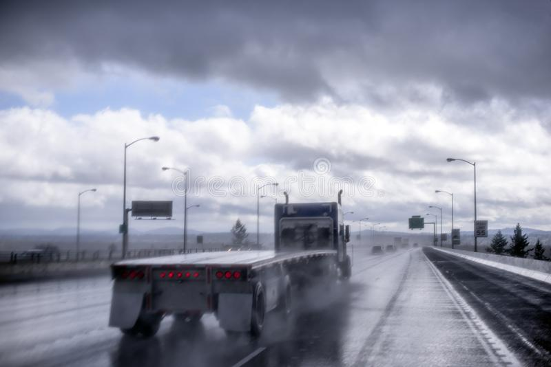 Big rig semi truck with empty flat bed semi trailer going on the raining highway with with rain dust spray. Big rig blue American classic bonnet long hauler semi royalty free stock image
