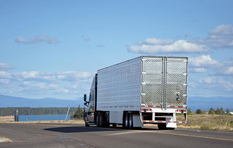 Big rig semi-truck with reefer semi trailer transporting cargo o. Dark big rig modern professional popular semi truck transporting perishable food in chilled stock image