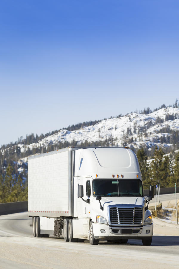Big Rig Semi Truck on snowy moutain pass. White Semi Truck 18-Wheeler on snowy mountain pass royalty free stock images