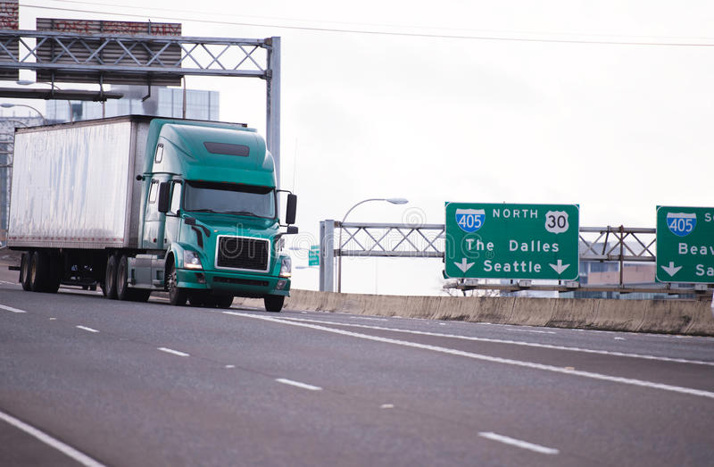 Big rig semi truck with trailer on wide interstate highway. Big rig green modern long haul semi truck with dry van trailer for delivering industrial volume of stock photography