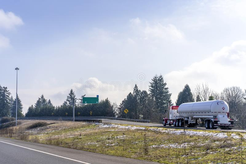Big rig semi truck transporting flammable and explosive chemical cargo in tank semi trailer running on the highway exit stock images
