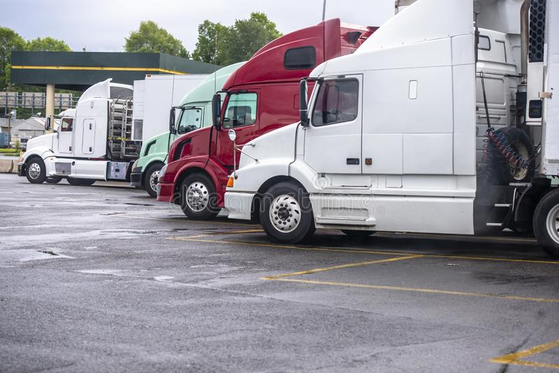 Big rig semi trucks standing in row on truck stop parking lot waiting for continuation of the planned route. Big rigs semi trucks of different make and model royalty free stock photography