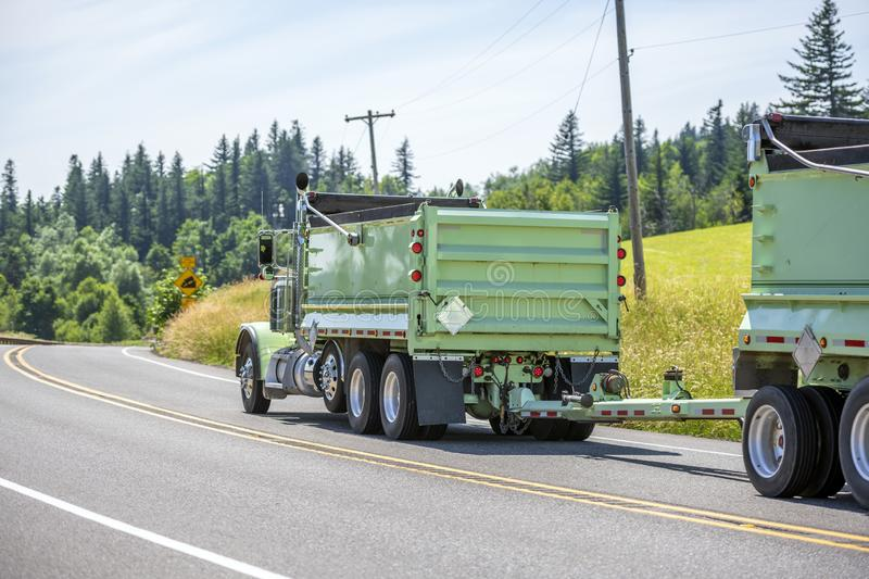 Big rig tip truck with two dump trailer driving on the road with hills and trees. Big rig powerful industrial brown tipper semi tuck tractor with two dump royalty free stock images