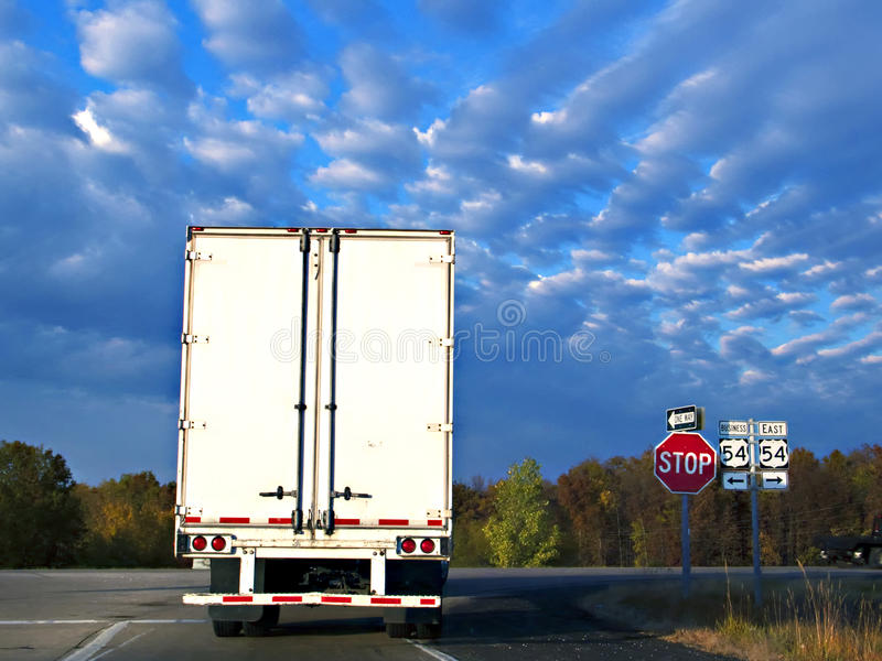 Big Rig Truck. Transporting commercial products, stopped at a stop sign on a country farm road in the midwestern United States with bold clouds in the sky