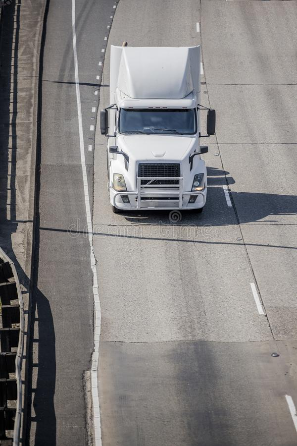 Big rig white bonnet semi truck tractor driving on the road to warehouse for pick up loaded semi trailer. Big rig white bonnet semi truck tractor with grille stock photo