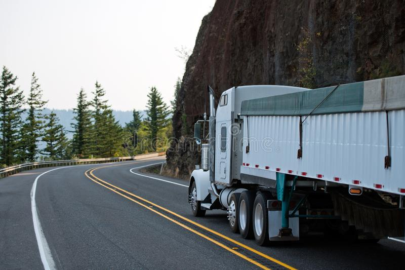 Big rig white semi truck with bulk covered semi trailer running royalty free stock photos