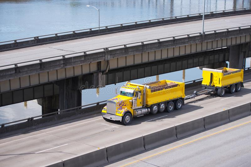 Big rig yellow tipper semi truck with dump trailer running on overpass intersection road along the river stock photo