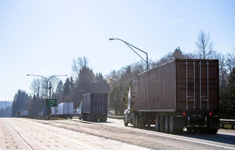Big rigs semi trucks standing in line to weight station for check truck weight and axle weight distribution stock photos