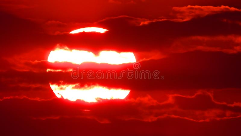 Big rising sun on a background of clouds. Big rising sun on a background of red clouds stock photography