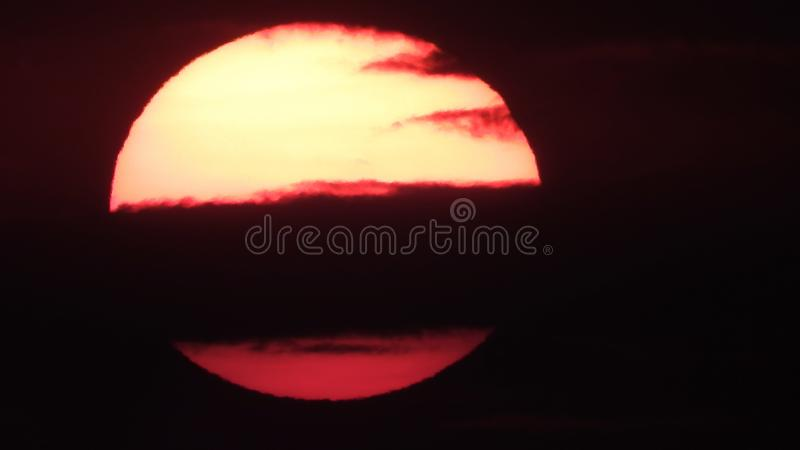 Big rising sun on a background of clouds. Big rising sun on a background of red clouds stock image