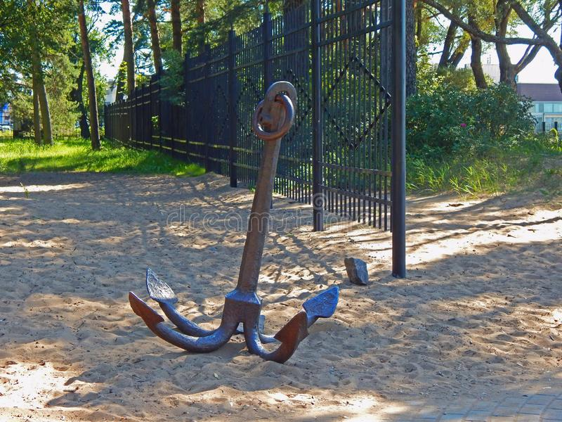 A big river anchor lying in the sand stock photo