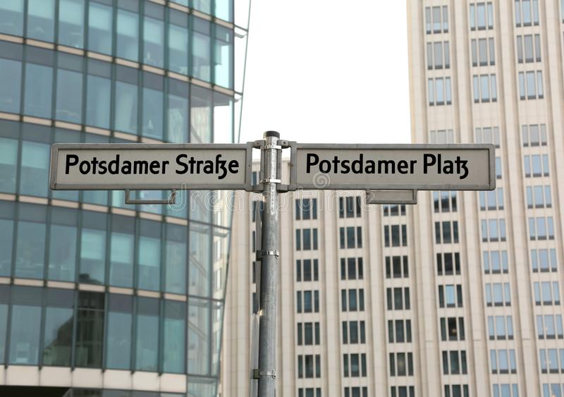 Big road signs with street name of Potsdamer Strasse and Platz t. Hat means PotsDam street and square in Berlin in Germany and many modern skyscrapers in royalty free stock photo