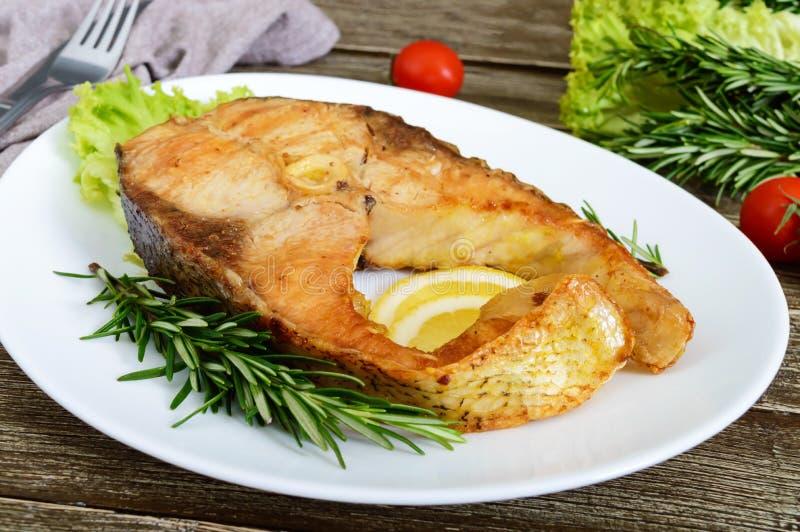 Big roasted carp steak with lemon and rosemary stock photos