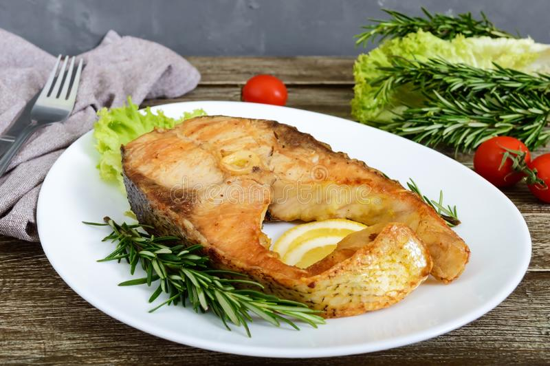 Big roasted carp steak with lemon and rosemary royalty free stock images