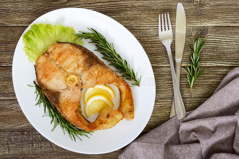 Big roasted carp steak with lemon and rosemary. Top view stock photography