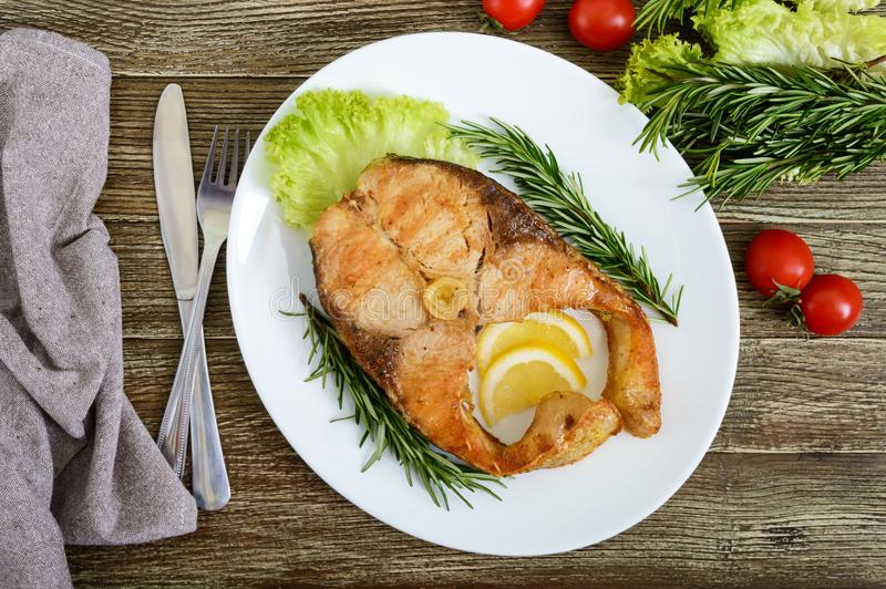Big roasted carp steak with lemon and rosemary stock photo