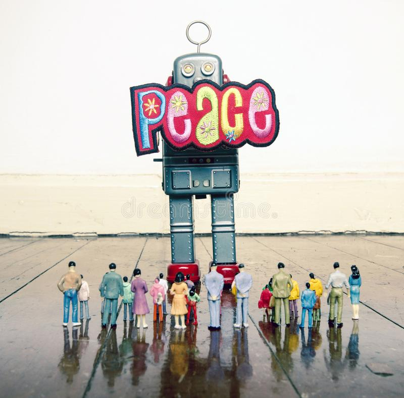 A big robot holding a peace sign to a crowd of plastc people. On a old wooden floor royalty free stock photography