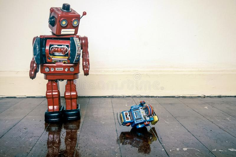 Big robot humiliates liitle one. Big retro robot toy humiliates little robot on a wooden floor with reflection royalty free stock image