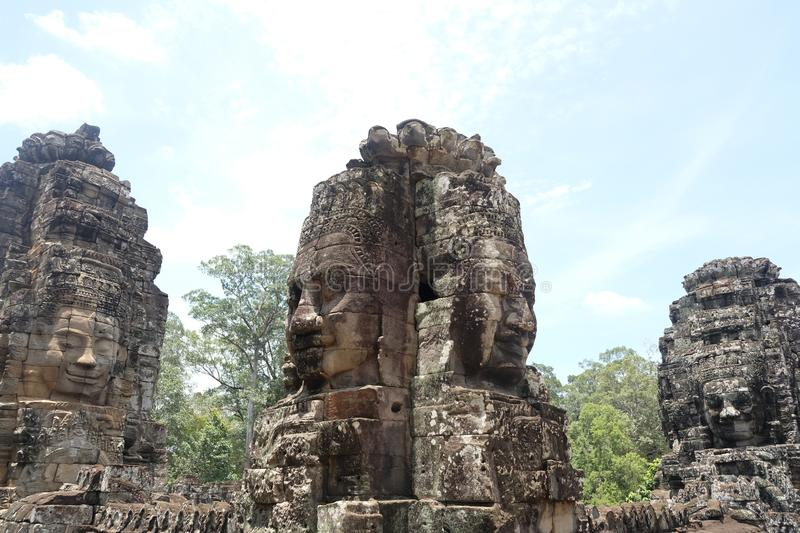 Rock faces in the temple of Bayon, Angkor, Cambodia. Big rock faces in Bayon temple, so beauiful and huge !!! 4 heads for one big statue. Buddhist temple in stock photography