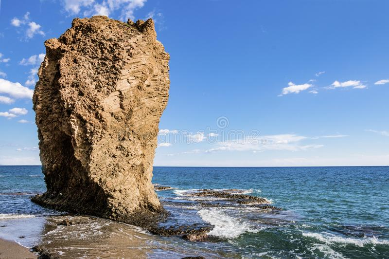 Big rock observing the sea. Big rock at a beach in Mojacar, south of Spain royalty free stock photos