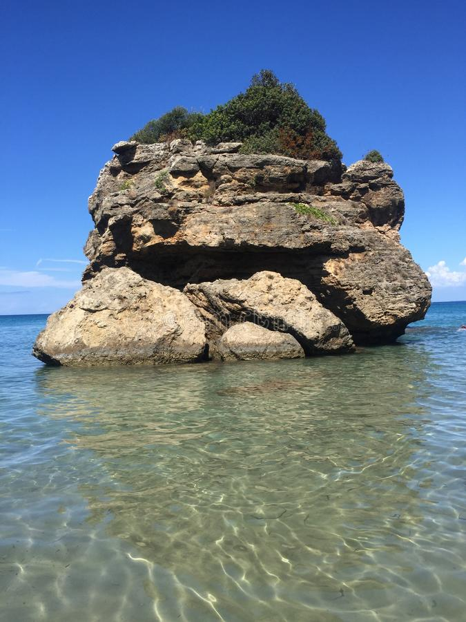 A big rock. In the sea with clear water stock images