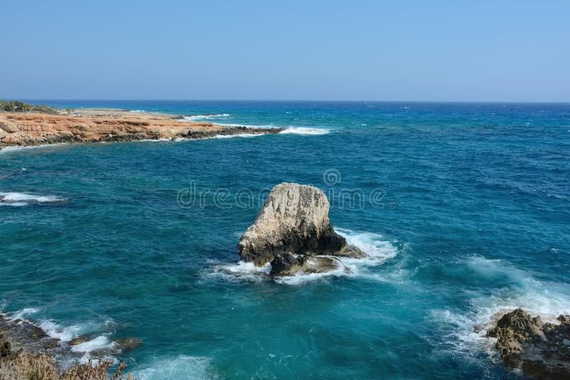 Big rock in the sea and waves with spray and foam, summer hot day stock images