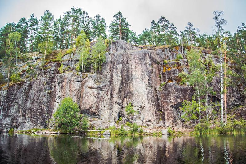 A big rock on the shore. Of the still water stock photos