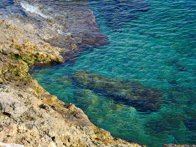 Big rocks by clear deep blue sea ocean Costa Blanca Spain. Summer vacation nature background image royalty free stock photos