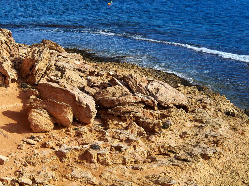 Big rocks by clear deep blue sea ocean Costa Blanca Spain. Summer vacation nature background image royalty free stock image