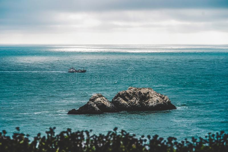 Big rocks in the middle of the sea and a coast guard sailing in the distance royalty free stock image